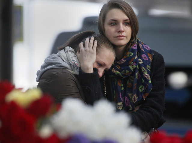 Young women grieve at an entrance of Pulkovo airport outside St.Petersburg, Russia, on Monday, November 2, 2015. In a massive outpouring of grief, thousands of people flocked to St. Petersburg's airport, laying flowers, soft toys and paper planes next to the pictures of the victims of the crash of a passenger jet in Egypt that killed all 224 on board in Russia's deadliest air crash to date.(Photo by Dmitry Lovetsk/AP Photo)