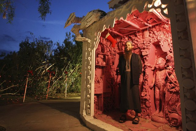 Artist Kenny Irwin Jr. stands among some of his creations in his Robolights art installation in Palm Springs, California December 15, 2014. The installation consists of hundreds of whimsical robot and other themed sculptures created from recycled materials including golf carts, kitchen appliances and microwaved smart phones, and is open to the public each holiday season on the sprawling Irwin family property. (Photo by David McNew/Reuters)