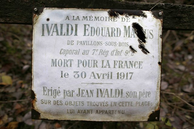 "A plaque hangs over the cross of the battlefield grave memorial of World War I French soldier Edouard Marius Ivaldi in Champagne, eastern France, November 3, 2015. The plaque which reads in part, ""In Memory of Edouard Marius Ivaldi, Corporal in the 7th Infantry  Regiment. Died for France on April 30, 1917"", was placed there by Ivaldi's father in 1919. World War One historians estimate that on the western front half of the fallen soldiers were never found or identified. (Photo by Charles Platiau/Reuters)"
