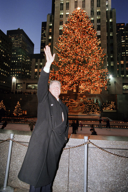 U.S. President Bill Clinton waves to well-wishers as he stops to view the Christmas Tree at Rockefeller Plaza in New York, Monday, December 13, 1993. Clinton, in town for a fund raiser for Sen. Patrick Moynihan, D-N.Y., took time out of his schedule to do some holiday shopping and take in some of the traditional sites. (Photo by Doug Mills/AP Photo)