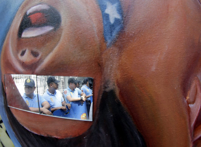 Filipino anti riot police are refected on a glass mounted on a protest placcard during a picket in front of the Philippine Supreme Court to coincide with its en banc session on the constitutionality of the Enhanced Defense Cooperation Agreement (EDCA) in Manila, Philippines, 10 November 2015. According to the statement of the protesters, they alledged that the EDCA will be presented as a gift to President Barack Obama when he visits the country to attend the APEC (Asia-Pacific Economic Cooperation) Summit. (Photo by Francis R. Malasig/EPA)