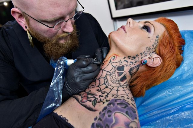 Pernille Ferdinandsen receives a neck tattoo from Peter Madsen during the third Copenhagen Ink Festival which opened Thursday May 9, 2013 in Copenhagen, Denmark, the biggest tattoo festival in Northern Europe. During the three days, 180 of the world's best and most celebrated national and international tattoo artists show the audience their skills in making art on the body and tattoo's on the audience. (Photo by Lars Krabbe/AP Photo)