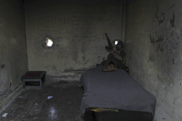 A rebel fighter holds his weapon as he sits at his position in the old city of Aleppo near the frontline against forces loyal to Syria's President Bashar al-Assad December 28, 2014. (Photo by Jalal Al-Mamo/Reuters)