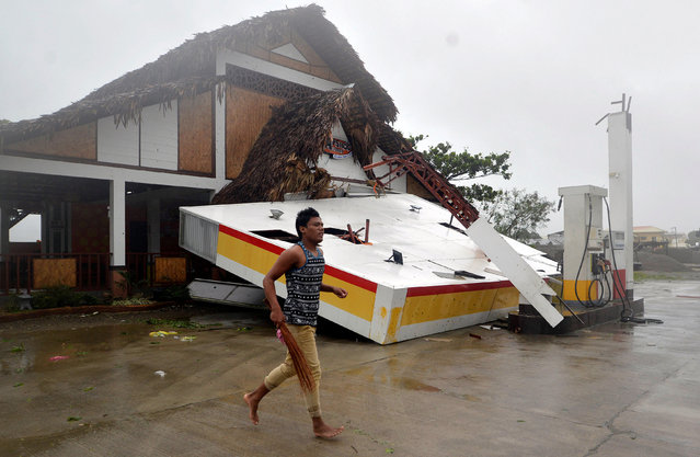 A resident runs past a collapsed roof of a petrol station after Typhoon Haima struck San Nicolas, Ilocos Norte in northern Philippines, October 20, 2016. (Photo by Ezra Acayan/Reuters)