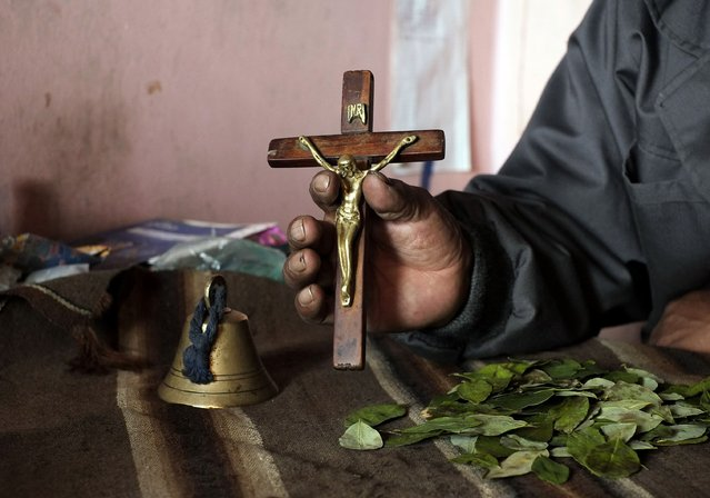 An Aymara withdoctor holds a crucifix to be used as part of a ritual at the witches market of El Alto, on the outskirts of La Paz, December 31, 2014. (Photo by David Mercado/Reuters)