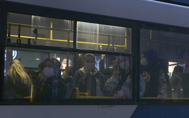 In this Thursday, November 12, 2020, file photo, commuters wearing masks to help protect against the spread of coronavirus, travel in a bus in Ankara, Turkey. (Photo by Burhan Ozbilici/AP Photo)