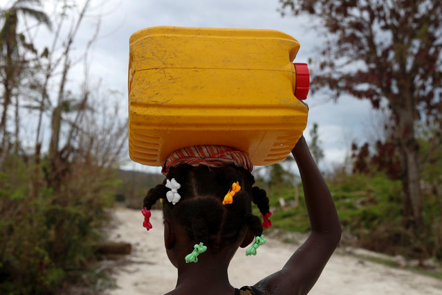 A girl carries a plastic container filled with water after Hurricane Matthew hit Jeremie, Haiti, October 19, 2016. (Photo by Carlos Garcia Rawlins/Reuters)