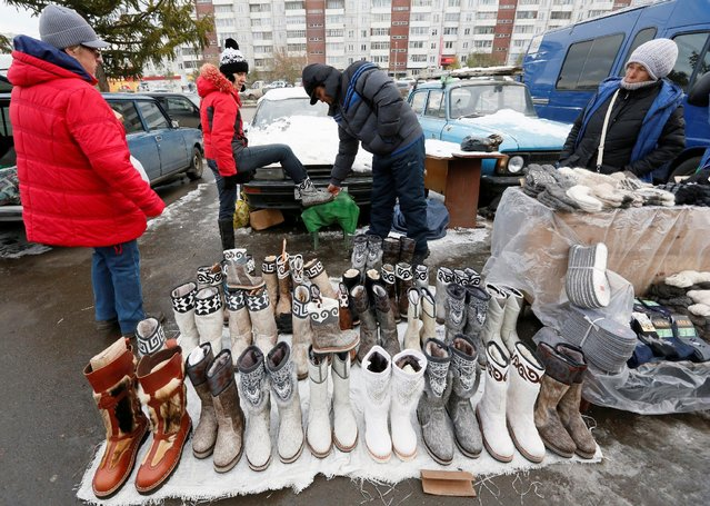 A vendor helps a client who tries on winter boots made of reindeer and wolf fur at a street market in Krasnoyarsk, Russia, October 17, 2016. (Photo by Ilya Naymushin/Reuters)