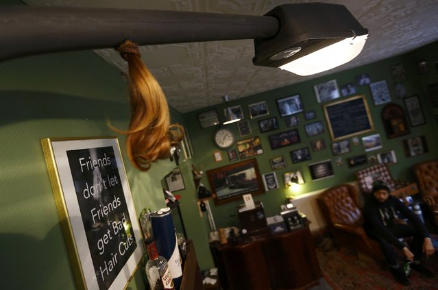 The cut off pony-tail of a customer hangs from an old street lamp illuminating Torreto barber shop in Frankfurt January 6, 2015. (Photo by Kai Pfaffenbach/Reuters)