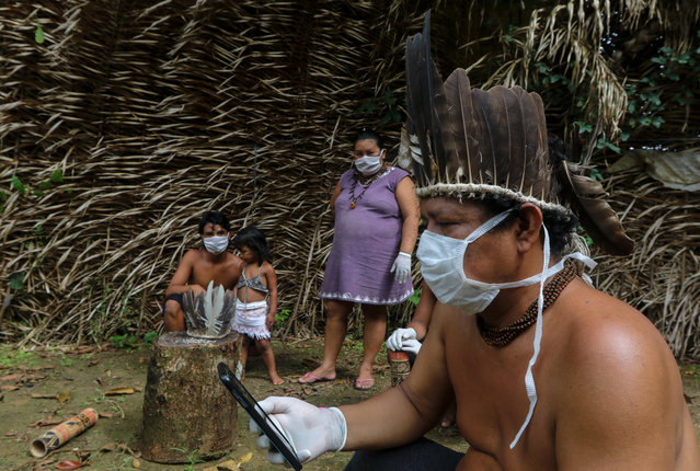 Satere-mawe indigenous people are seen using a smartphone to contact a doctor in Sao Paulo state to receive medical guidance amid the COVID-19 novel coronavirus pandemic at the Sahu-Ape community, 80 km of Manaus, Amazonas State, Brazil, on May 5, 2020. The Brazilian state of Amazonas, home to most of the country's indigenous people, is one of the regions worst affected by the pandemic, with more than 500 deaths to date according to the health ministry. (Photo by Ricardo Oliveira/AFP Photo)