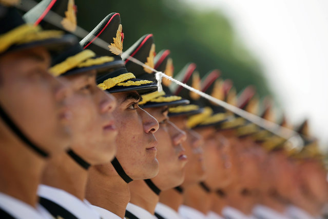 Honour guards stand behind a string used to ensure that they stand in a straight line, outside the Great Hall of the People before the welcome ceremony for Germany Chancellor Angela Merkel, in Beijing, China May 24, 2018. (Photo by Jason Lee/Reuters)