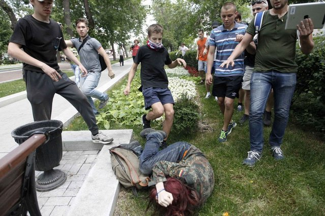 """Youths kick a gay rights activist during a protest against a proposed new law termed by the State Duma, the lower house of Parliament, as """"against advocating the rejection of traditional family values"""" in central Moscow June 11, 2013. (Photo by Maxim Shemetov/Reuters)"""