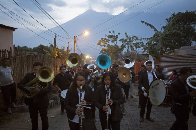 Musicians accompany to the cemetery the funeral procession for seven people who died during the eruption of the Volcan del Fuego, which in Spanish means Volcano of Fire, in the background, in San Juan Alotenango, Guatemala, Monday, June 4, 2018. Residents of villages skirting the volcano began mourning the dead after an eruption buried them in searing ash and mud. (Photo by Luis Soto/AP Photo)