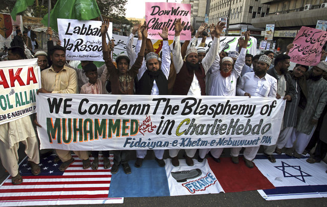 Supporters of a Pakistani religious group 'Fidaiyan-e-Khetm-e-Nebuwwat' stand on the representations of American, French and Israeli flags and chant slogans during a demonstration to protest against caricatures published in French magazine Charlie Hebdo, in Karachi, Pakistan, Saturday, January 17, 2015. (Photo by Fareed Khan/AP Photo)