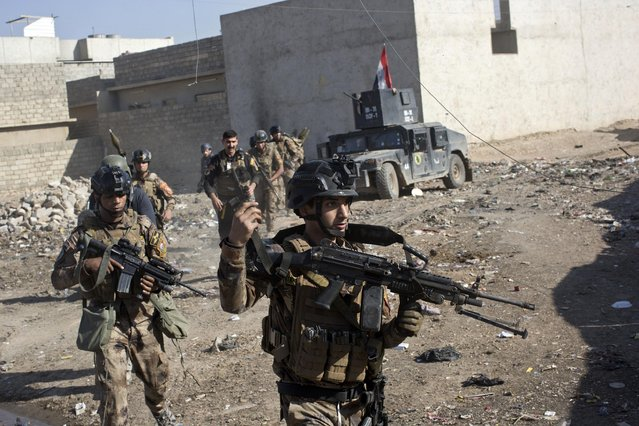 Iraqi special forces soldiers move in formation in an alley on the outskirts of Mosul, Iraq, Friday, November 4, 2016. Heavy fighting erupted in the eastern neighborhoods of Mosul on Friday as Iraqi special forces launched an assault deeper into the urban areas of the city and swung round to attack Islamic State militants from a second entry point, to the northeast. (Marko Drobnjakovic/AP Photo)