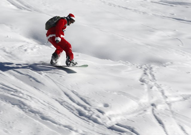 A man, dressed as Santa Claus, speeds down during a promotional event on the opening weekend in the alpine ski resort of Verbier, Switzerland, December 6, 2015. (Photo by Denis Balibouse/Reuters)