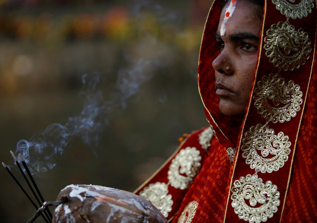 """A devotee holds burning incense while offering prayer to the setting sun during the """"Chhat"""" festival at Bagmati River in Kathmandu, Nepal November 6, 2016. (Photo by Navesh Chitrakar/Reuters)"""