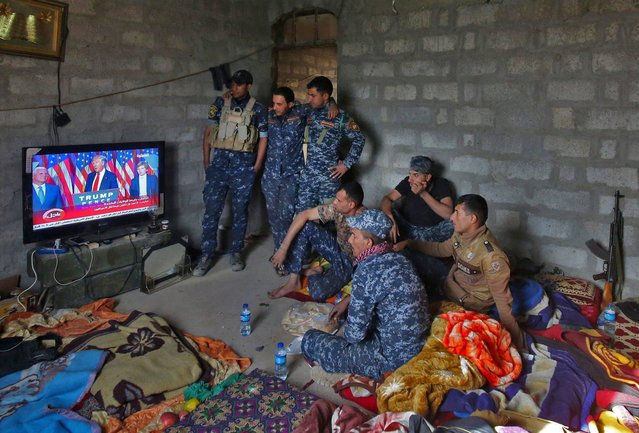 Members of the Iraqi forces watch Donald Trump giving a speech after he won the US president elections in the village of Arbid on the southern outskirts of Mosul on November 9, 2016, as they rest in a house during the ongoing military operation to retake Mosul from the Islamic State (IS) group. Iraqi Prime Minister Haider al-Abadi congratulated Donald Trump on his election as president and said he hoped for continued US and international support in the war against jihadists. (Photo by Ahmad Al-Rubaye/AFP Photo)