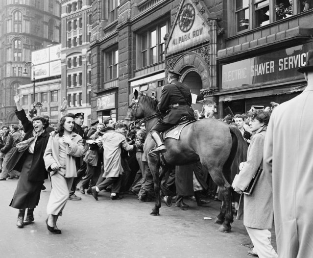Two Girls who managed to evade the police walk away as police on foot and horseback push back to te curd at Park Row, In New York on April 26, 1960, A milling throng of more than 1,000 High students who storned city hall in a Demonstration supporting teachers wage demands. (Photo by AP Photo)