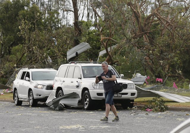 A man takes pictures of damage to cars following a rare tornado in the Sydney suburb of Kurnell, December 16, 2015. (Photo by Jason Reed/Reuters)