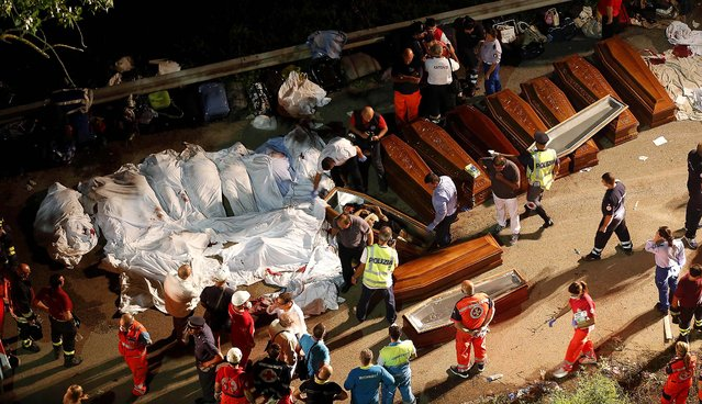 Coffins are lined up near the wreckage of the bus, on July 29, 2013. (Photo by Salvatore Laporta/Associated Press)