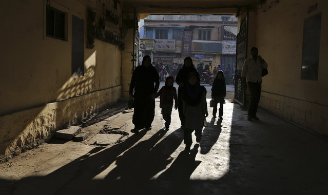 Indian children are silhouetted as they  arrive with elders to attend their school in  Bangalore, India, Wednesday, February 4, 2015. India's Right To Education Act promises free, compulsory schooling to all children ages 6 to 14, but millions of children still don't go to school and many who do are getting only the barest of educations. (Photo by Aijaz Rahi/AP Photo)