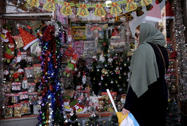 An Iranian woman walks past Christmas decorations at a shop in central Tehran December 23, 2015. (Photo by Raheb Homavandi/Reuters)