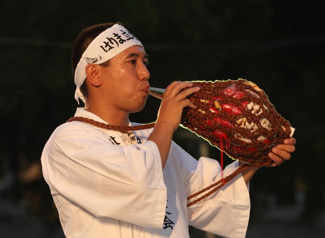 A man performs horagi, conch shell trumpet during the annual Himeji Castle Festival on August 3, 2013 in Himeji, Japan. The parade of Castle Queens is part of the traditional matsuri festival around the UNESCO world heritage Himeji Castle. (Photo by Buddhika Weerasinghe/Getty Images)