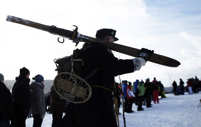 "A participant carries his skis for the ""Nostalgic Ski Race"" in the western town of Neuastenberg February 8, 2015. (Photo by Ina Fassbender/Reuters)"