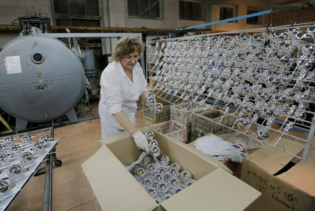 """An employee boxes up glass spheres for Christmas and New Year decorations coated with a layer of aluminum, at the """"Yolochka"""" (Christmas tree) factory, which has been producing glass decorations and toys for the festive season since 1848, in the town of Klin outside Moscow, Russia, November 24, 2016. (Photo by Maxim Zmeyev/Reuters)"""