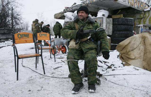 A pro-Russian separatist sits on a chair at a checkpoint in the town of Vuhlehirsk, eastern Ukraine February 10, 2015. At the front in Vuhlehirsk, a small town captured by rebels last week, volleys of artillery crashed in both directions. The rebels are pushing to encircle government forces holding out in nearby Debaltseve, a rail hub that is the main rebel target. (Photo by Maxim Shemetov/Reuters)
