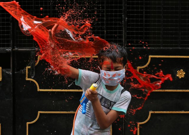 A boy wearing a protective face mask reacts as he is splashed with coloured water during Holi celebrations, amidst the spread of the coronavirus disease (COVID-19), in Chennai, India, March 29, 2021. (Photo by P. Ravikumar/Reuters)