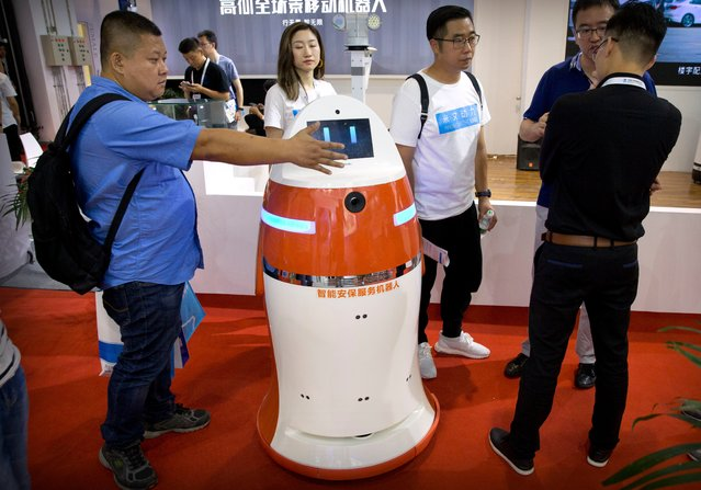 A visitor sticks his hand in front of a patrolling security robot from Chinese robot maker Hunan Wanwei Intelligent Robot Technology Co. at the World Robot Conference in Beijing, China, Wednesday, August 15, 2018. (Photo by Mark Schiefelbein/AP Photo)