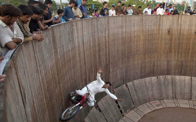"""People watch a man demonstrate his motorcycle skills inside the """"well of death"""" at a fair set up on the occasion of the Eid al-Fitr holiday in Rawalpindi, Pakistan, Monday, August 12, 2013. (Photo by B. K. Bangash/AP Photo)"""
