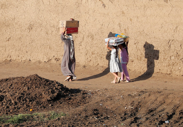 An Egyptian farmer and her daughters carry boxes of fruits on their heads near fields on the outskirts of Cairo, Egypt April 27, 2018. (Photo by Amr Abdallah Dalsh/Reuters)