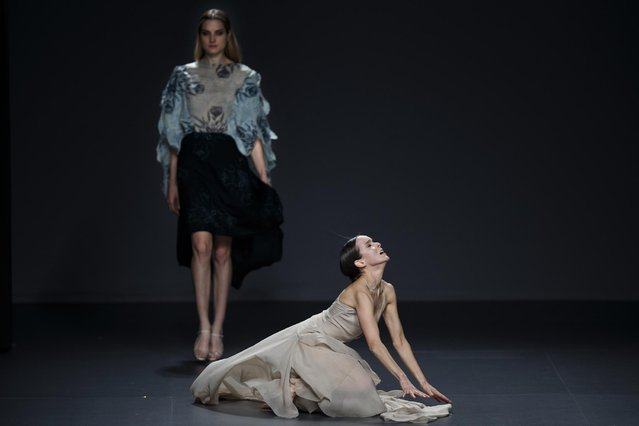A woman dances while a model displays an Autumn/Winter design by Maria Cle Leal during the EGO for young designers at Madrid's Fashion Week in Madrid, Spain, Wednesday, February 11, 2015 . (Photo by Daniel Ochoa de Olza/AP Photo)