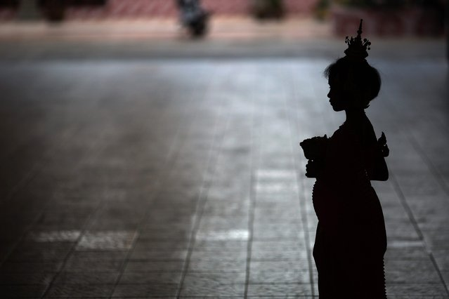 A girl, wearing traditional clothes, waits for brides and grooms to arrive to Wat Takien temple in Nonthaburi province, on the outskirts of Bangkok February 14, 2015. (Photo by Damir Sagolj/Reuters)