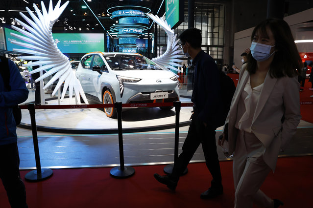 Attendees pass by a vehicle from the GAC Group displayed during the Shanghai Auto Show in Shanghai on Monday, April 19, 2021. (Photo by Ng Han Guan/AP Photo)
