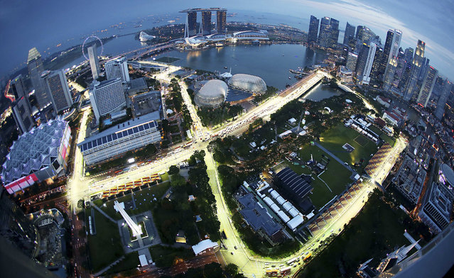 This aerial photo made using a fisheye lens shows the Singapore F1 Grand Prix's Marina Bay City Circuit at dusk from Swissotel The Stamford in Singapore, Tuesday, September 17, 2013. The F1 race is slated for September 21-23. (Photo by Wong Maye-E/AP Photo)