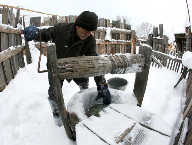 Mikhail Baburin, 66, takes water from a well at a court yard of his house in the remote Siberian village of Mikhailovka, Krasnoyarsk region, Russia, December 5, 2016. (Photo by Ilya Naymushin/Reuters)