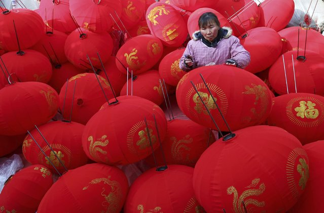 A worker makes red lanterns as orders hike ahead of the Spring Festival, at a workshop in Wenxian county, Henan province February 11, 2015. (Photo by Reuters/China Daily)