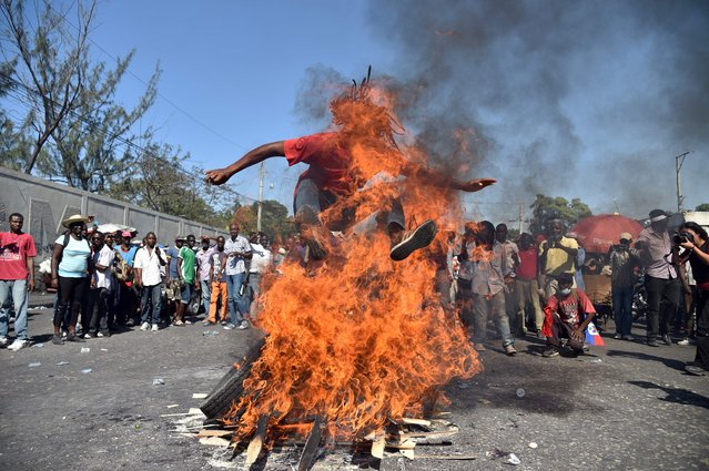 A man jumps over the fire while perform a voodoo ceremony prior a protest for the streets of Port-au-Prince, on January 19, 2016. Demonstrators are protesting against the presidential run-off and to demand a transitional government, denouncing fraud in the first round of presidential elections held October 25. The second round of presidential elections is scheduled for January 24 between ruling party candidate Jovenel Moise and Jude Celestin. Celestin has said he does not want to participate in the January 24th run-off against ruling party candidate Jovenel Moise, has yet to submit his official resignation to the Provisional Electoral Council(CEP). (Photo by Hector Retamal/AFP Photo)