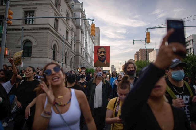Black Lives Matter (BLM) protesters hold placards and shout slogans during a march on the anniversary of the death of George Floyd, in Brooklyn, New York on May 25, 2021. The family of George Floyd appealed on May 25 for sweeping police reform on the anniversary of the African American man's murder by a white officer, as they met President Joe Biden at the White House. (Photo by Ed Jones/AFP Photo)
