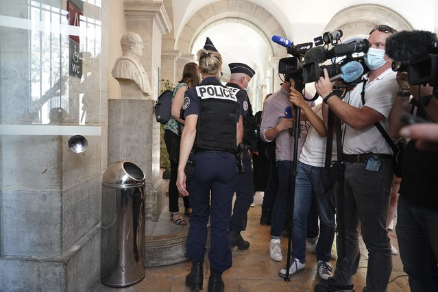 """Police officers leave the courtroom as the man who slapped French President Emmanuel Macron is tried, Thursday, June 10, 2021 in Valence, central France. The 28-year-old Frenchman who described himself as a right-wing or extreme-right """"patriot"""" was sentenced to four months in prison Thursday for slapping President Emmanuel Macron in the face. (Photo by Laurent Cirpriani/AP Photo)"""