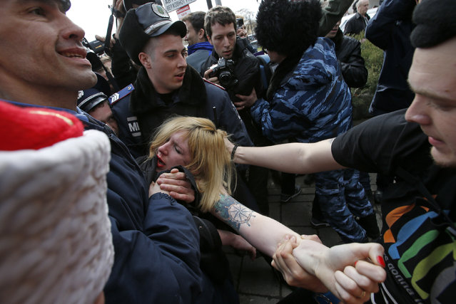 Members of Crimean self-defense units and Interior Ministry members block a topless activist from the Ukrainian feminist group FEMEN, who is taking part in an anti-war protest, near the Crimean parliament building in Simferopol, March 6, 2014. (Photo by David Mdzinarishvili/Reuters)