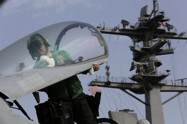 A U.S. sailor cleans the cockpit of a military jet aboard the USS Carl Vinson aircraft carrier in the Persian Gulf, Thursday, March 19, 2015. (Photo by Hasan Jamali/AP Photo)