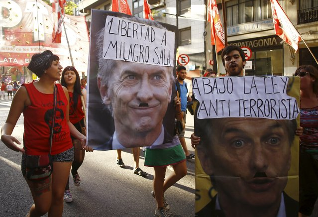 "Protesters carry signs depicting Argentine President Mauricio Macri that read ""Freedom for Milagro Sala"" (L) and ""Down the anti-terrorism law"" during a march to show solidarity for social leader Milagro Sala in Buenos Aires, Argentina, January, 27, 2016. Sala, the president of Tupac Amaru Neighbourhood Association, was imprisoned in the northwestern Argentine province of Jujuy on January 16, 2016 on charges of public disturbance and inciting crimes. (Photo by Enrique Marcarian/Reuters)"