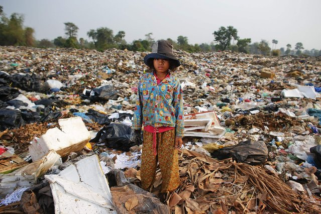 Soburn, an 11-year-old girl, poses for a picture while collecting what can be used as food for pigs at landfill dumpsite outside Siem Reap March 19, 2015. (Photo by Athit Perawongmetha/Reuters)