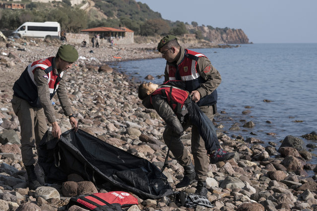 A Turkish paramilitary police officer holds the lifeless body of a migrant boy near the Aegean town of Ayvacik, Canakkale, Turkey, Saturday, January 30, 2016. (Photo by Halit Onur Sandal/AP Photo)
