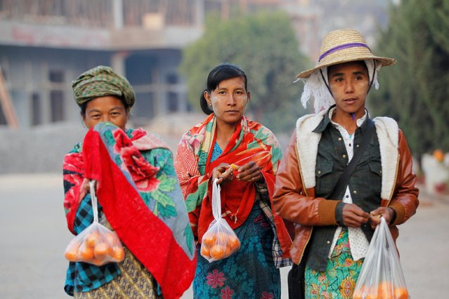 Refugees who fled from violence in Laukkai, Kokang region, hold bags of oranges at a temporary refugee camp set up in a monastery in Lashio February 19, 2015. (Photo by Soe Zeya Tun/Reuters)